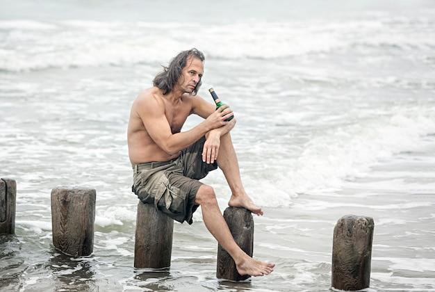 Alcoolismo. homem de meia-idade com o torso nu sentado em postes de madeira na praia e bebendo álcool