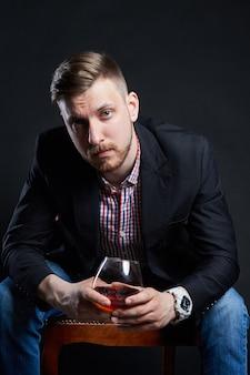Alcoolismo masculino, homem com copo de álcool na mão