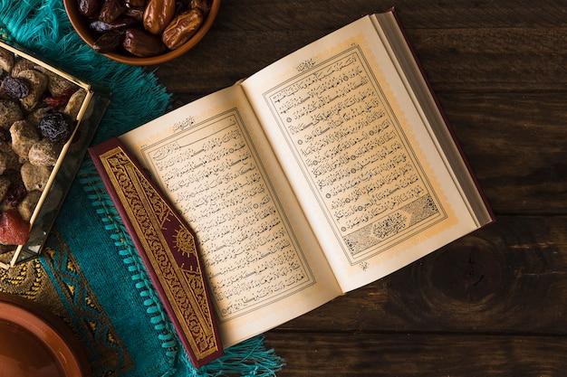 Alcorão aberto perto de sobremesas árabes