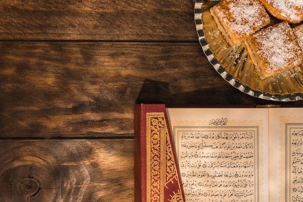 Alcorão deitado perto de sobremesa árabe