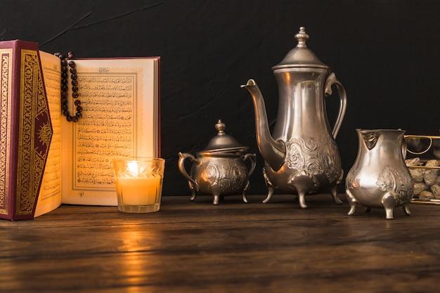 Alcorão e vela perto de conjunto de chá