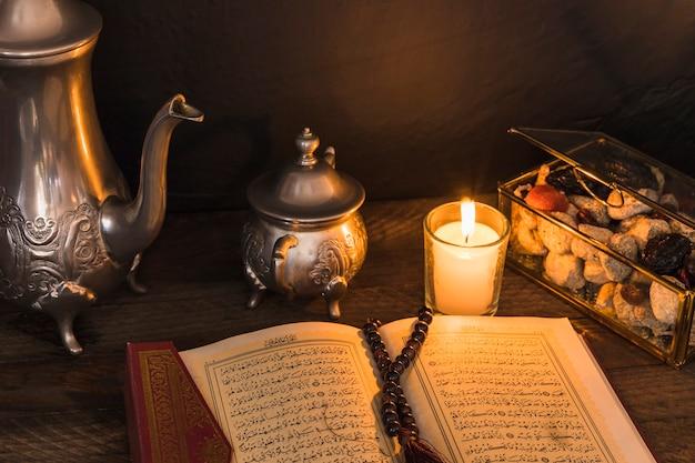 Alcorão e vela perto de doces e jogo de chá