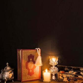 Alcorão e velas perto de doce