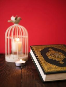 Alcorão na mesa com suporte de vela de gaiola vintage