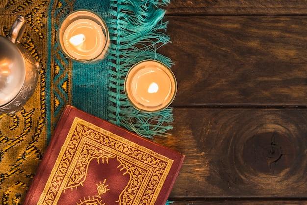 Alcorão perto de velas e pote a arder
