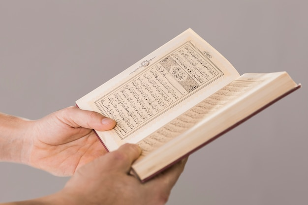 Alcorão sendo realizado em close-up de mãos