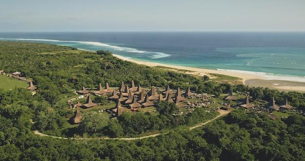 Aldeia aérea tradicional com casas de telhados ornamentados na costa de areia do mar