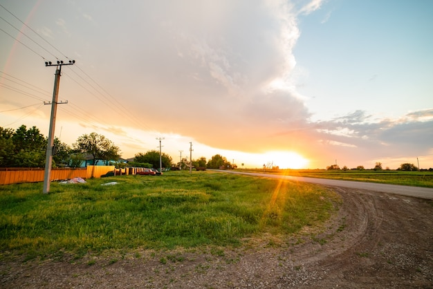 Aldeia da rússia, pôr do sol na primavera, sol brilhante, postes e cabos