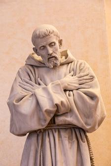 Aldeia de assis na região de umbria, itália. estátua de são francisco. a cidade é famosa pela mais importante basílica italiana dedicada a são francisco - san francesco.