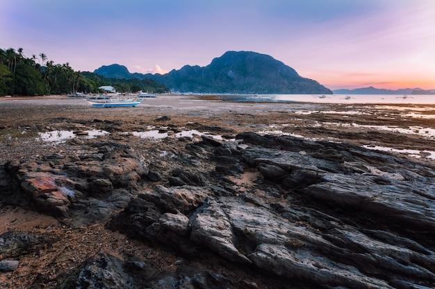 Aldeia de el nido com barcos banca locais na costa iluminados pela luz do pôr do sol na maré baixa. cenário pitoresco da natureza. palawan, filipinas.