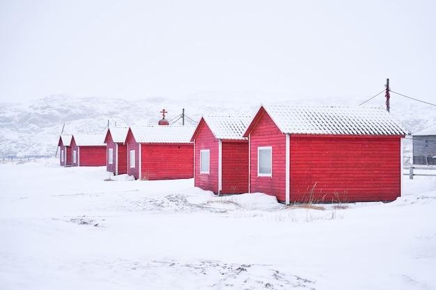Aldeia de madeira vermelha na paisagem de inverno