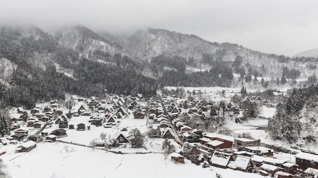 Aldeia de shirakawago com neve cair na temporada de inverno