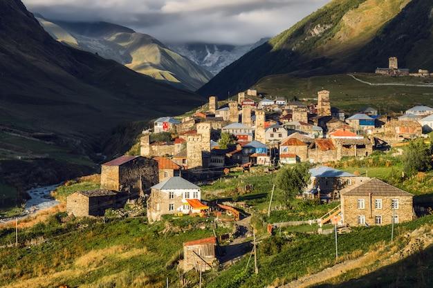 Aldeia de ushguli com uma montanha de shkhara, se escondendo nas nuvens no fundo. comunidades chvibiani e zhibiani.