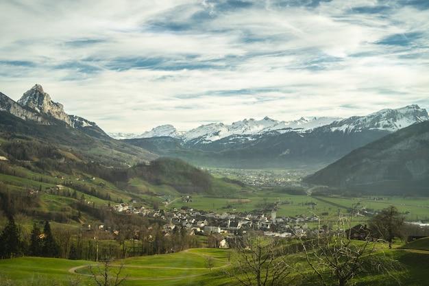Aldeia em um belo vale com montanhas cobertas de neve