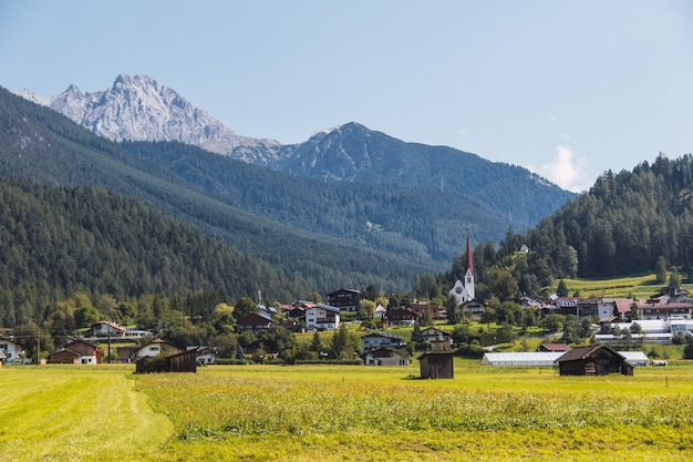Aldeia em um prado de montanha. prado verde e montanhas