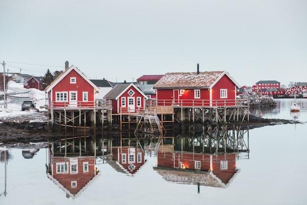 Aldeia escandinava com reflexão de casa vermelha no oceano ártico