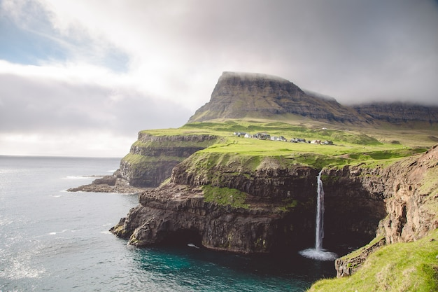 Aldeia gasadalur e bela cachoeira. vagar, ilhas faroe, dinamarca.