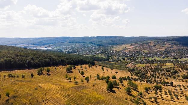 Aldeia localizada nas terras baixas, árvores raras e floresta em primeiro plano com colinas