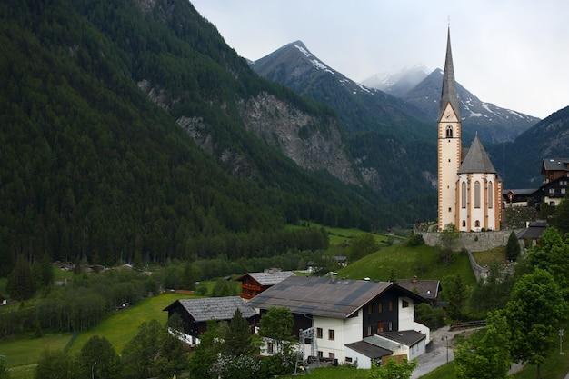 Aldeia na montanha com a igreja nos alpes
