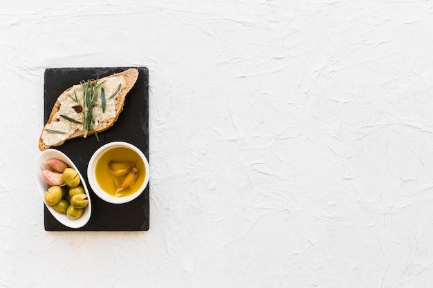 Alecrim e queijo no pão com azeite e azeitonas na tigela sobre a placa de ardósia