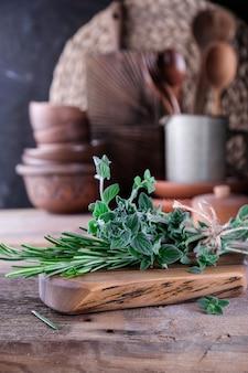 Alecrim fresco e tomilho em uma tábua de madeira. cozinha em estilo retro