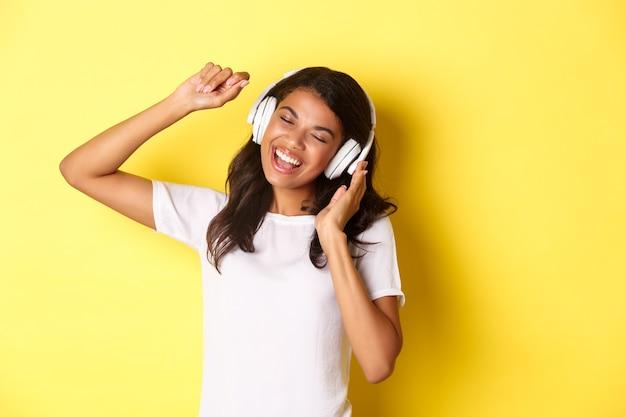Alegre adolescente afro-americana ouvindo música em fones de ouvido, dançando e cantando alegremente