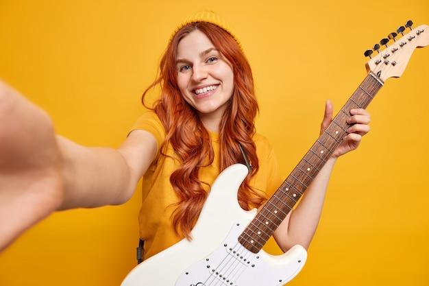 Alegre adolescente ruiva estende o braço para fazer selfie sorrisos de alegria com os dentes contentes por comprar uma nova guitarra elétrica branca, usa roupas casuais e vai praticar tocando instrumento musical