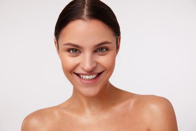Alegre adorável jovem morena com maquiagem natural posando, mostrando suas emoções agradáveis e sorrindo amplamente