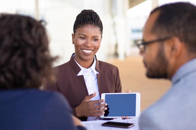 Alegre agente de vendas bem-sucedido, apresentando conteúdo no tablet