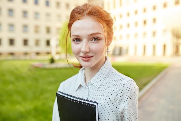 Alegre aluna atraente jovem com sardas e cadernos de pé e sorrindo
