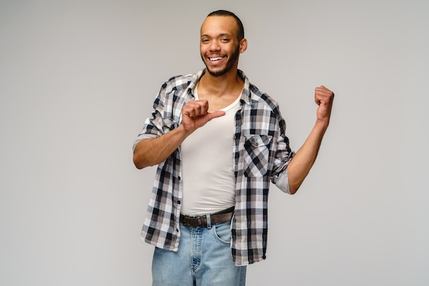 Alegre amigável jovem afro-americano iwearing camisa casual, apontando com o dedo no espaço da cópia.