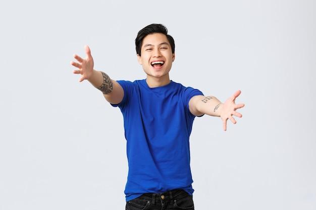 Alegre amigável jovem estudante do sexo masculino, homem asiático em t-shirt azul com tatuagens, estendendo as mãos em direção à câmera para um abraço, quer abraços ou abraços, cumprimentando querido amigo, plano de fundo cinza.