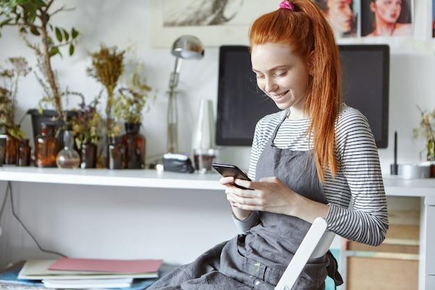 Alegre artista feminina jovem bonita no avental cinza relaxante na cadeira com gadget durante pequenas férias enquanto trabalhava na pintura na oficina