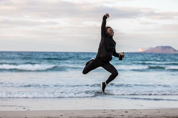 Alegre atleta negra pulando perto do mar