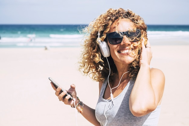 Alegre atraente linda caucasiana de meia-idade mulher sorrindo na praia em um lugar tropical enquanto ouve música com o telefone inteligente. pessoas curtindo férias e liberdade do trabalho, férias