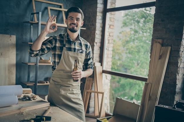 Alegre barbudo homem positivo mostrando sinal de ok no avental camisa quadriculada segurando uma garrafa de cerveja depois de terminar o trabalho em madeira
