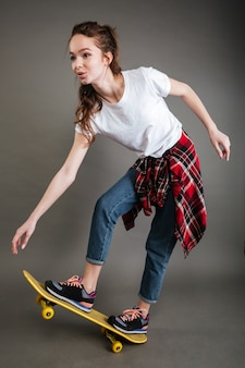 Alegre bela jovem andando de skate e se divertindo
