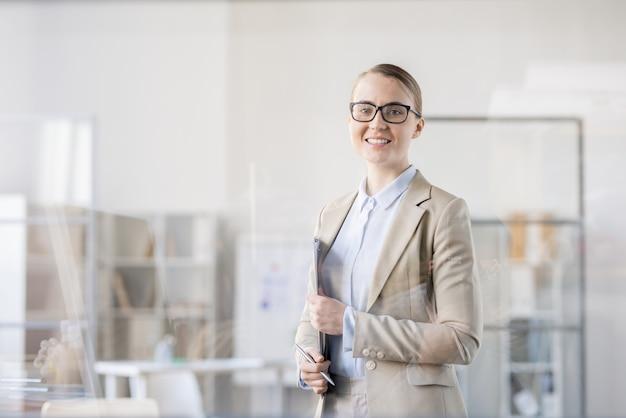 Alegre bem-sucedida jovem analista de negócios em trajes formais em um escritório moderno segurando uma prancheta