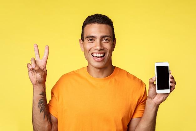 Alegre bonitão moderno com tatuagem no braço, segurando o smartphone, mostrando a tela do celular e fazer sinal de paz, sorrindo satisfeito, gabar fotos de viagem de férias, aplicativo de conselhos, promover a loja online