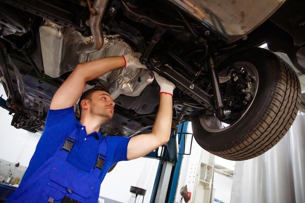 Alegre, bonito e confiante especialista em reparos de automóveis em macacões conserta e substitui peças velhas por novas em um carro em um elevador em serviço