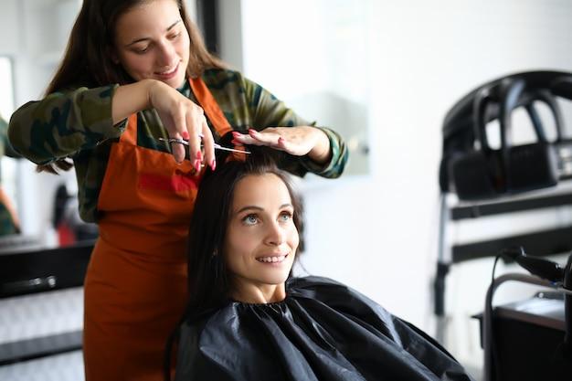 Alegre cabeleireira feminina no avental corta o cabelo brevemente para visitante com uma tesoura. cliente satisfeito, senta-se na cadeira com a capa preta e olha para cima.