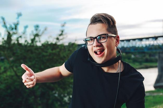 Alegre cara sorridente posando com fones de ouvido ao ar livre