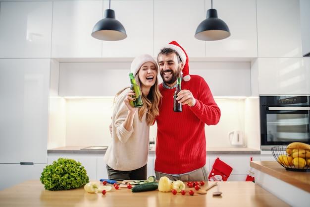 Alegre casal adorável dançando na cozinha e segurando a cerveja