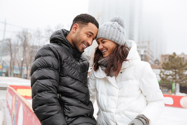 Alegre casal apaixonado patinando na pista de gelo ao ar livre.