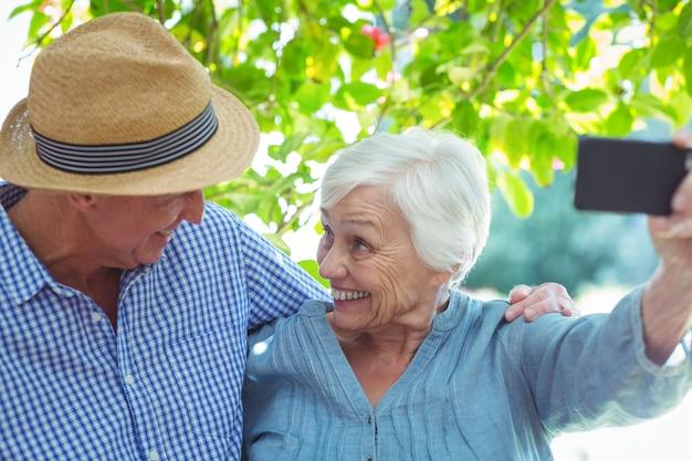 Alegre casal aposentado tendo auto-retrato