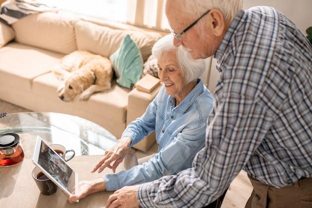 Alegre casal de idosos usando tablet digital