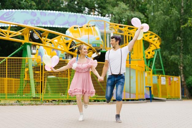 Alegre casal feliz segurando balões, correndo e sorrindo