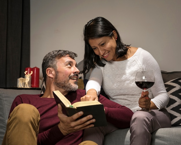 Alegre casal sênior bebendo e lendo juntos