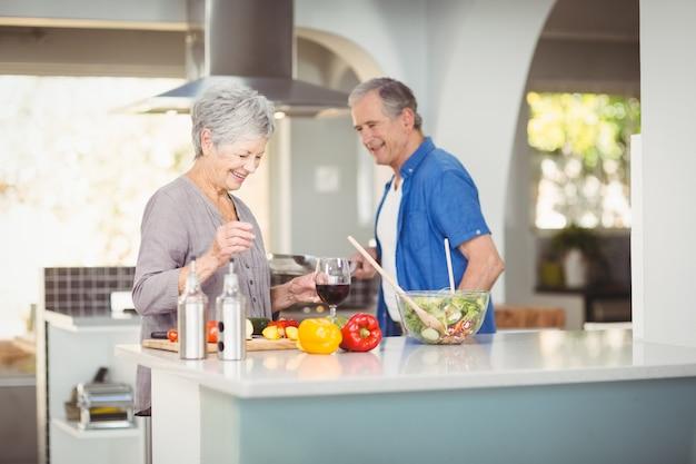 Alegre casal sênior preparando uma salada