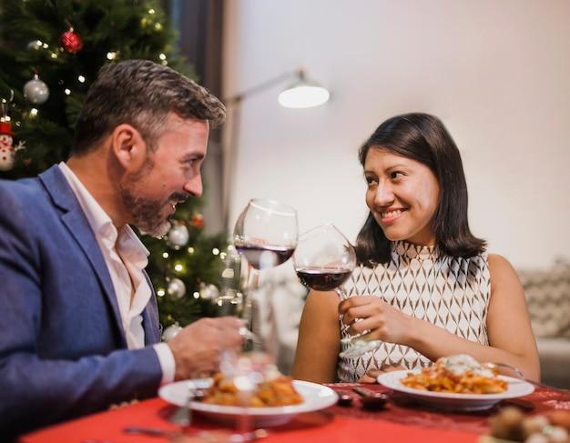 Alegre casal sênior torcendo no jantar